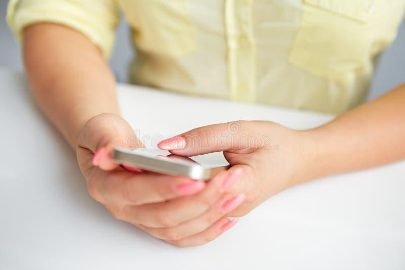 Weibliche Hand, die einen Handy hält lizenzfreie stockfotos