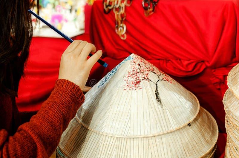 Weibliche Hand, die einen Hut des traditionellen Chinesen malt stockfoto