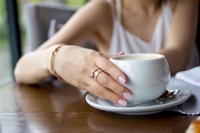 Weibliche Hand, die einen Tasse Kaffee hält stockfotografie
