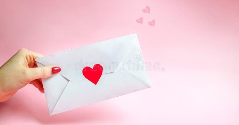 Weibliche Hand, die einen Umschlag mit einem roten Herzen hält Ein Liebesbrief zum geliebten Roter heart-shaped Schmucksachegesch lizenzfreie stockfotografie