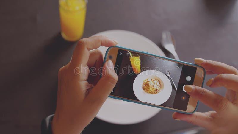 Weibliche Hand, die einige Fotos von ihrem Mobile eines köstlichen italienischen Lebensmitteltellers macht Abschluss oben stockbild