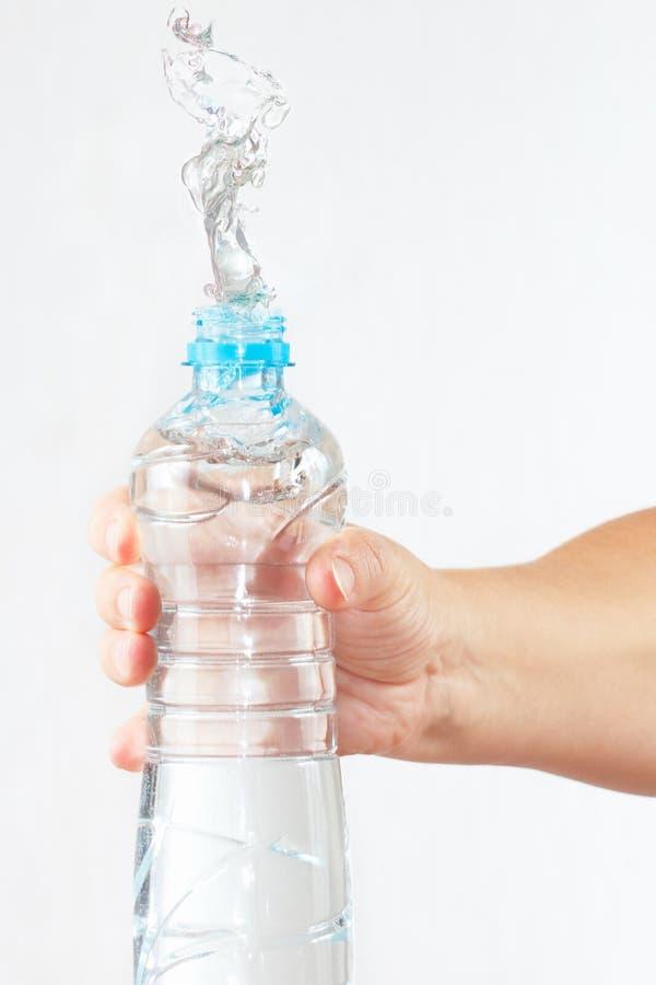 Weibliche Hand, die Flasche Wasser mit einem Spritzen rüttelt lizenzfreies stockfoto