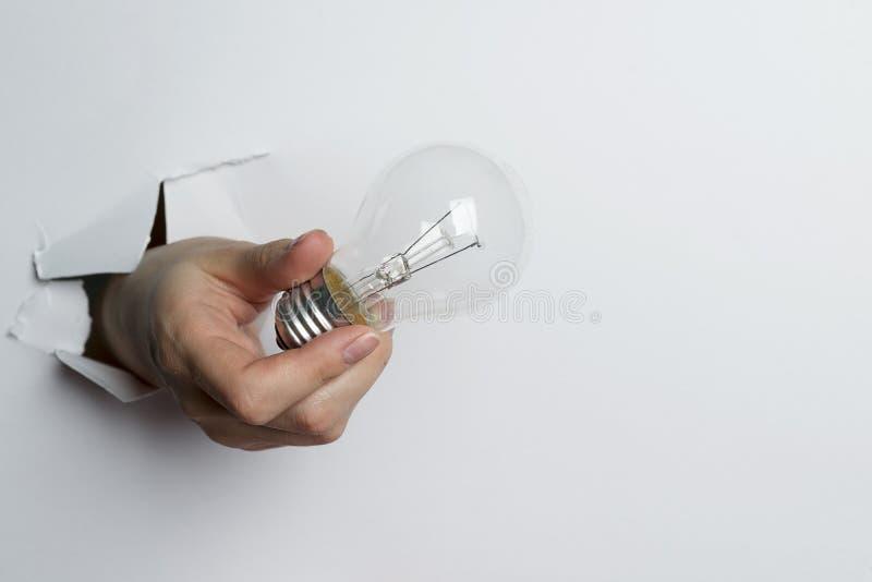 Weibliche Hand, die Glühlampe auf weißem Hintergrund hält lizenzfreie stockbilder