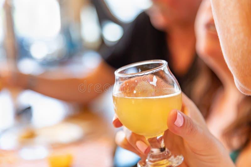 Weibliche Hand, die Glas Mikrogebräu-Bier an der Bar hält stockbilder