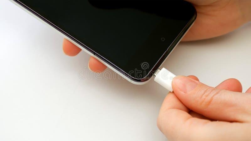 Weibliche Hand, die Ladegeräthandy Smartphone verstopft lizenzfreie stockbilder