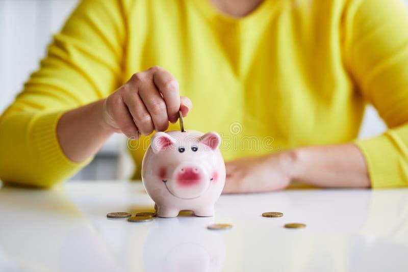 Weibliche Hand, die Münze in Sparschwein setzt stockfoto
