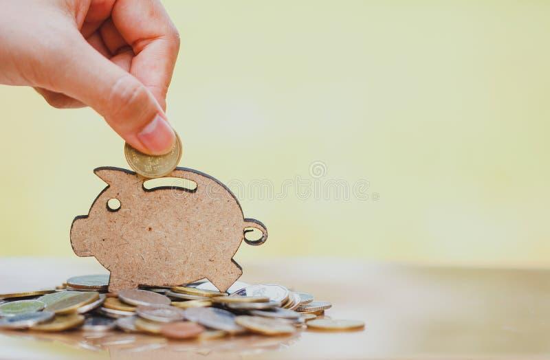 Weibliche Hand, die Münze und Stapel Münzen in Konzept von Einsparungen und von Geldwachsen oder von Energieabwehr einsetzt stockbild