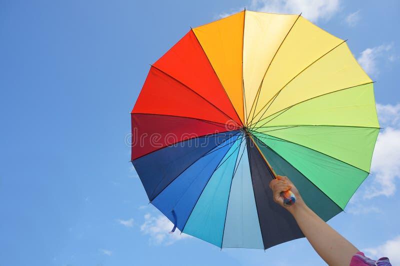 Weibliche Hand, die mehrfarbigen Regenschirm hält stockbilder