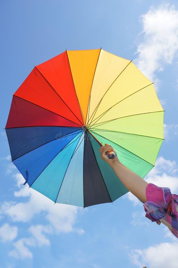 Weibliche Hand, die mehrfarbigen Regenschirm hält stockfoto