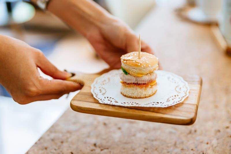 Weibliche Hand, die Mini Chicken Burger auf hölzernem hackendem Brett mit Unschärfehintergrund dient lizenzfreies stockfoto