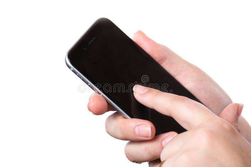 Weibliche Hand, die modernes schwarzes intelligentes Mobiltelefon mit dem leeren Bildschirm lokalisiert auf einem weißen Hintergr lizenzfreie stockfotografie