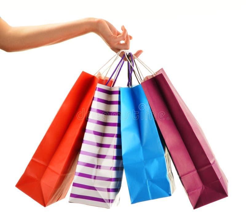 Weibliche Hand, die Papiereinkaufstaschen lokalisiert auf Weiß hält lizenzfreie stockfotografie
