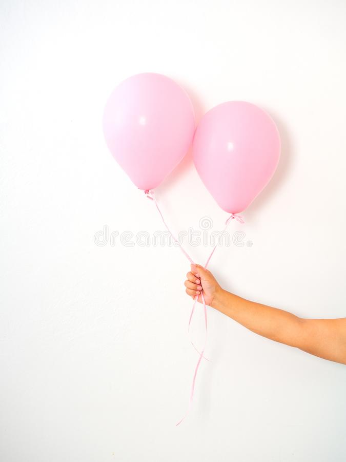 Weibliche Hand, die rosa Ballone hält lizenzfreie stockfotografie