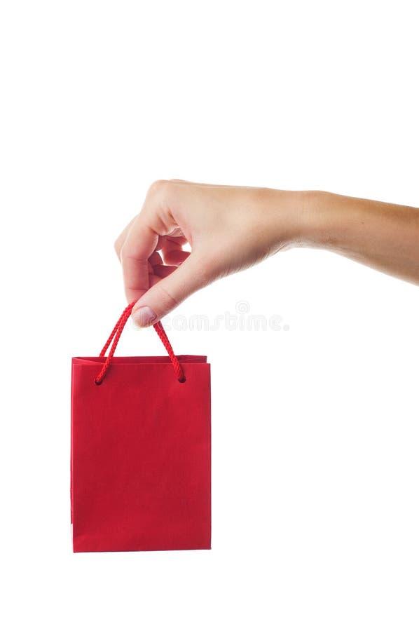 Weibliche Hand, die roten Geschenkbeutel anhält lizenzfreie stockfotografie