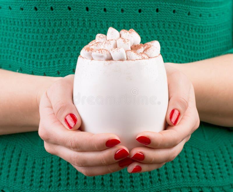 Weibliche Hand, die Schale heiße Schokolade mit Eibisch hält stockfotos