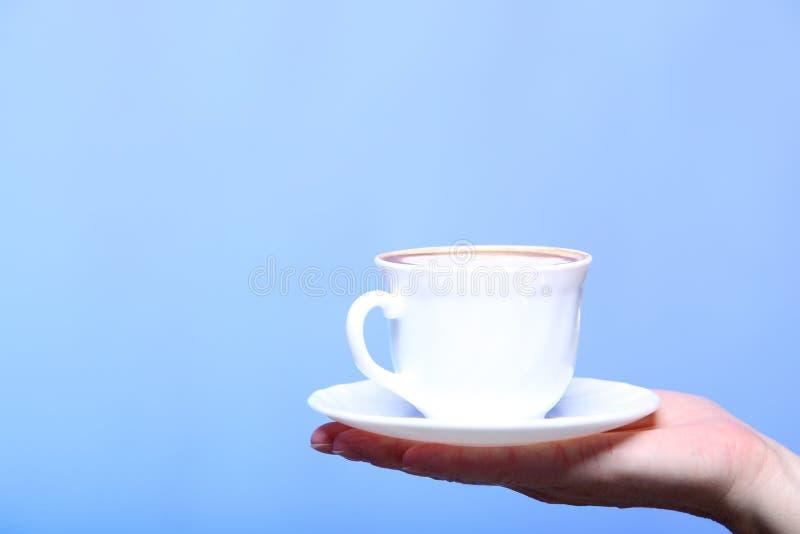 Weibliche Hand, die Schale heißen Lattekaffeecappuccino hält stockfotografie