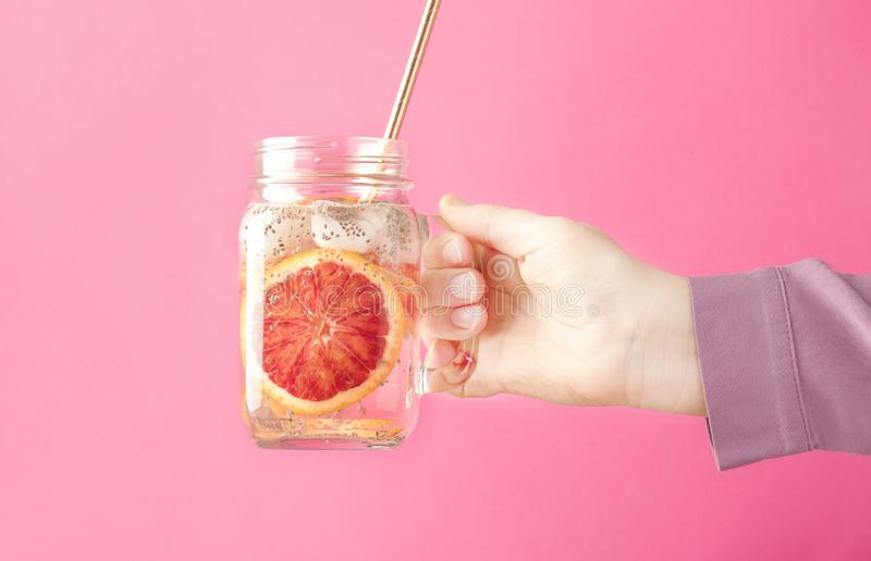 Weibliche Hand, die Sommergetränk mit Soda, orange Scheibe und chia Samen im Glasgefäß auf rosa Hintergrund, selektiver Fokus häl stockfoto