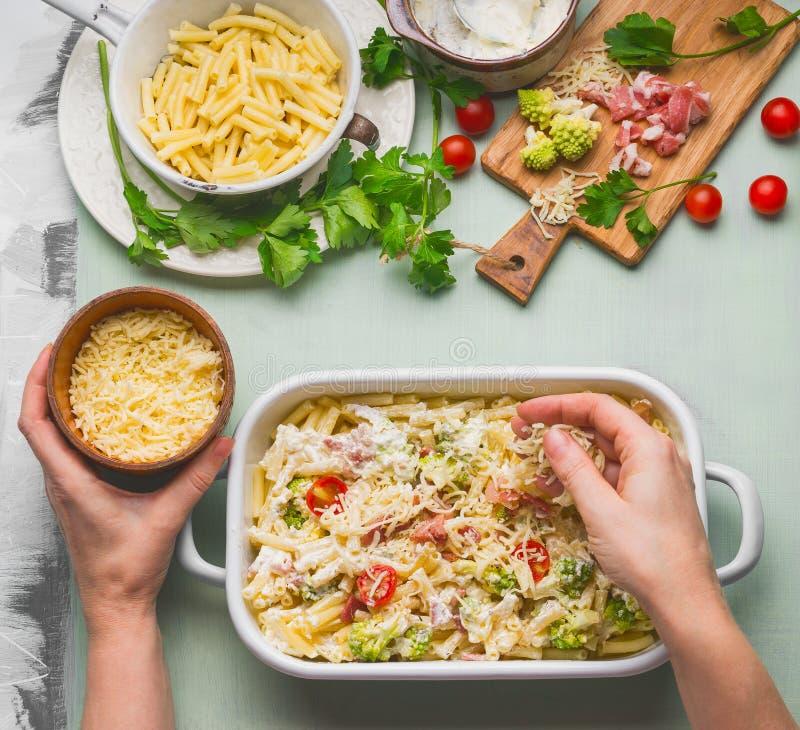 Weibliche Hand, die Teigwarenkasserolle mit Tomate, Speck und Käse, Draufsicht macht lizenzfreies stockfoto