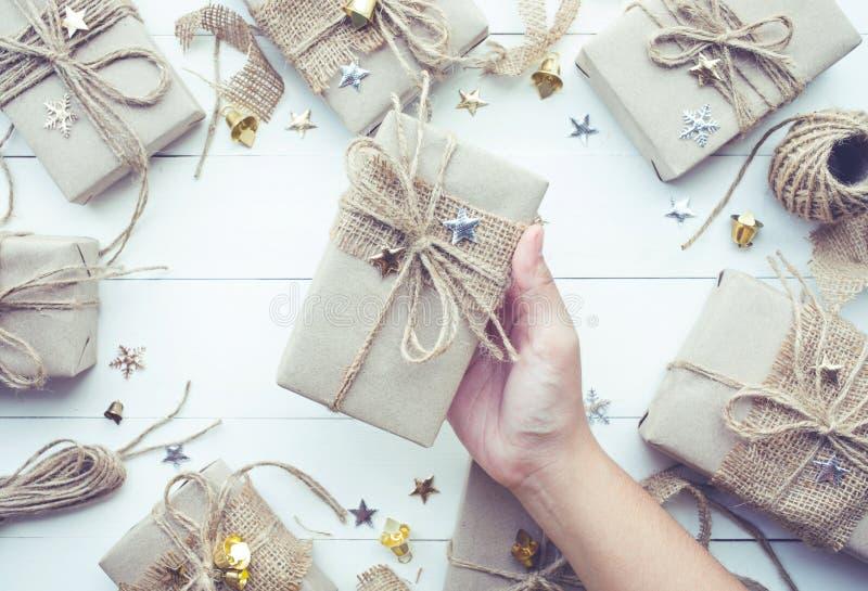 Weibliche Hand, die Weihnachtsgeschenkgeschenkbox hält ansammlung stockfoto