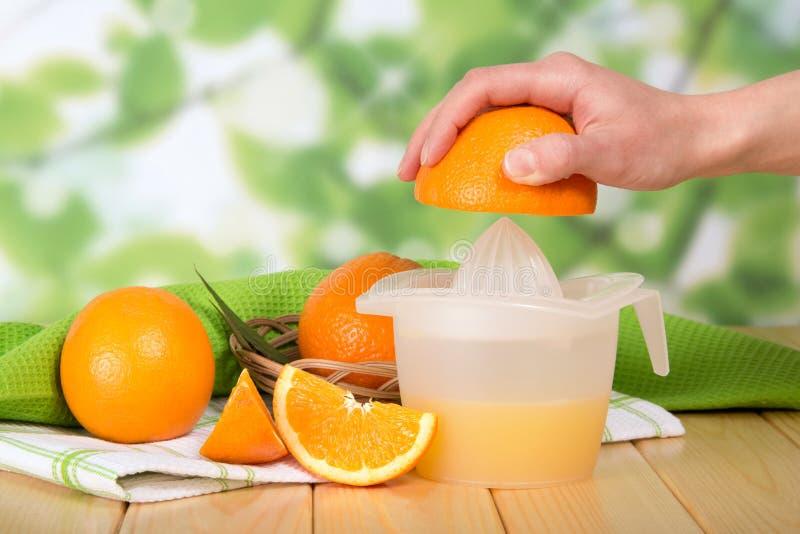 Weibliche Hand drückt einen Orange eigenhändig Juicer zusammen stockfoto