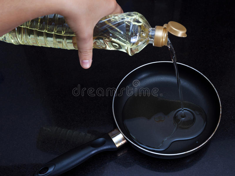 Weibliche Hand gießt Pflanzenöl auf einer Bratpfanne lizenzfreie stockbilder