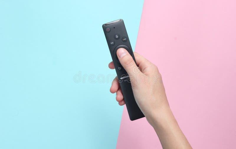 Weibliche Hand hält die Fernsehdirektübertragung auf einem Rosablauen Pastellhintergrund Beschneidungspfad eingeschlossen stockbild