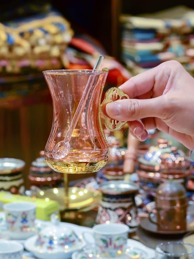 Weibliche Hand hält ein türkisches Teeglas der Andenkens mit einem Löffel lizenzfreies stockfoto