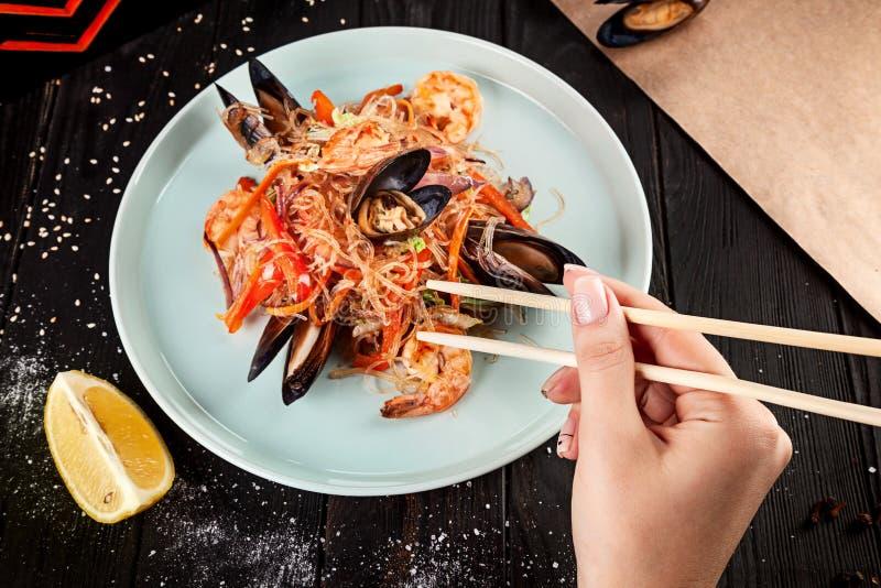 Weibliche Hand hält Essstäbchen, um chinesische Nudeln mit Miesmuscheln zu essen lizenzfreie stockbilder