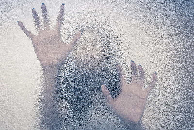 Weibliche Hand Halloweens hinter transparentem Glas stockfotos