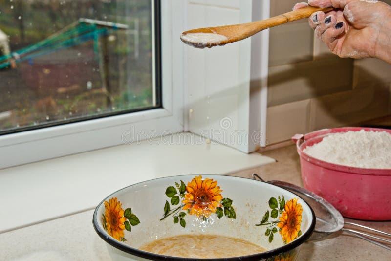 Weibliche Hand knetet Teig von der Milch von Butter und von Mehl in einer Metallsch?ssel mit einem h?lzernen Schneebesen in der K lizenzfreie stockfotografie