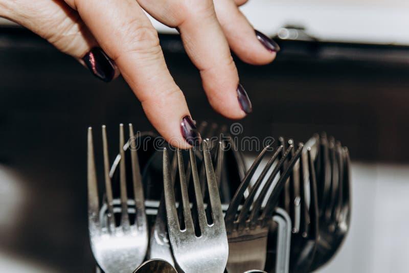 Weibliche Hand legt die Teller in einer offenen Sp?lmaschinennahaufnahme, die mit den sauberen, gewaschenen Tellern verstopft wir stockbilder