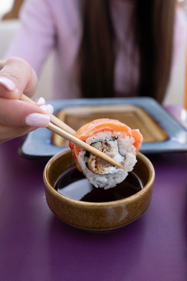 Weibliche Hand mahnt Sushi in der Sojasoße Das Mädchen isst Sushi und Rollen mit Essstäbchen lizenzfreie stockfotos