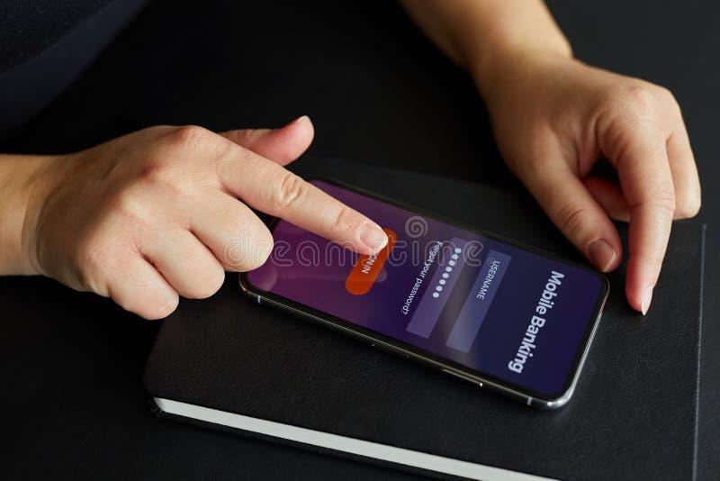 Weibliche Hand meldet sich bewegliches Bankwesen an lizenzfreies stockfoto