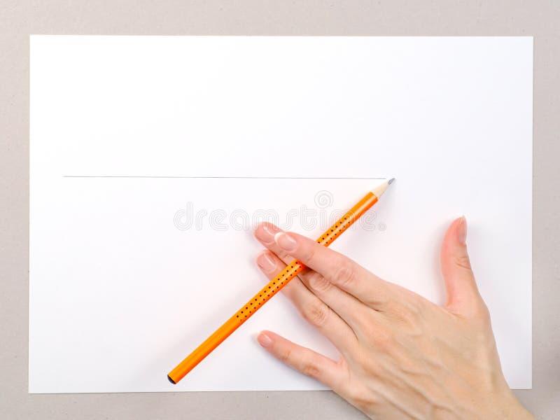 Weibliche Hand mit Bleistift auf Weißbuchblatt stockfoto