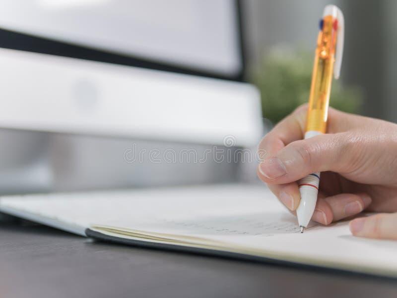 Weibliche Hand mit dem Stift, der Anmerkungen auf Tabelle in Büro schreibt stockbilder