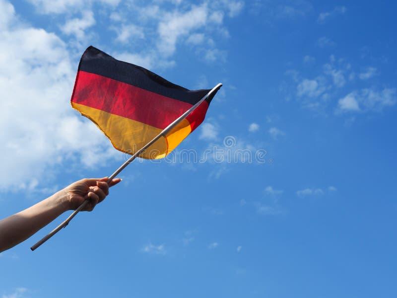 Weibliche Hand mit der deutschen Flagge stockfotografie