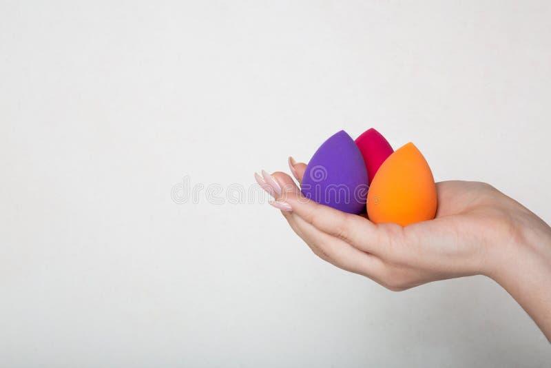 Weibliche Hand mit der netten Maniküre halten purpurrot, Rosa und orange Schönheitsmischmaschinen Raum für Text stockbilder