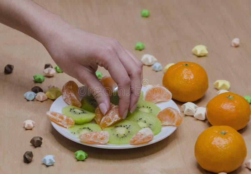 Weibliche Hand mit einer Scheibe von Tangerinen stockfotografie