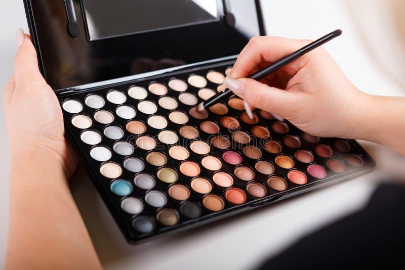 Weibliche Hand mit Make-upbürste und -farben lizenzfreies stockbild