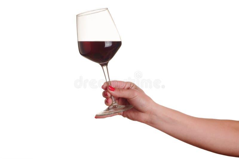 Weibliche Hand mit Rotweinglas lizenzfreie stockbilder