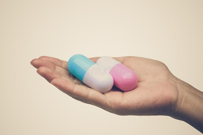 Weibliche Hand mit zwei Kapselmedikamenten stockbild