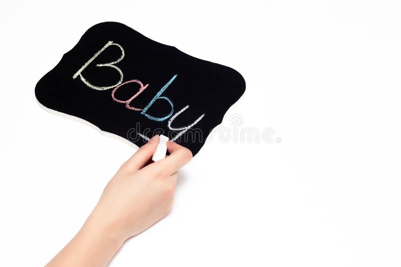 Weibliche Hand schreibt in Kreide auf eine Tablette das Wortkind, das Konzept der Annahme und die Träume eines Kindes, Unfruchtba stockfotografie