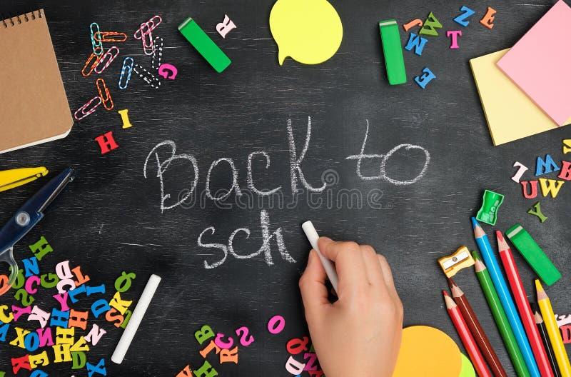 weibliche Hand schreibt mit einer weißen Kreide auf eine Tafel zurück zu Schule stockfotos