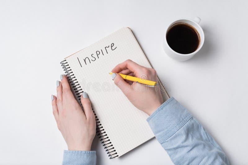 Weibliche Hand schreibt Wörter Inspire in Copybook Notepad, Stift und Kaffee auf weißem Hintergrund stockbild