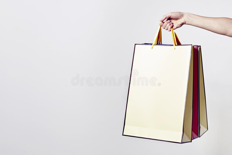Weibliche Hand, welche die Einkaufstaschen, lokalisiert auf Weiß hält lizenzfreie stockfotografie