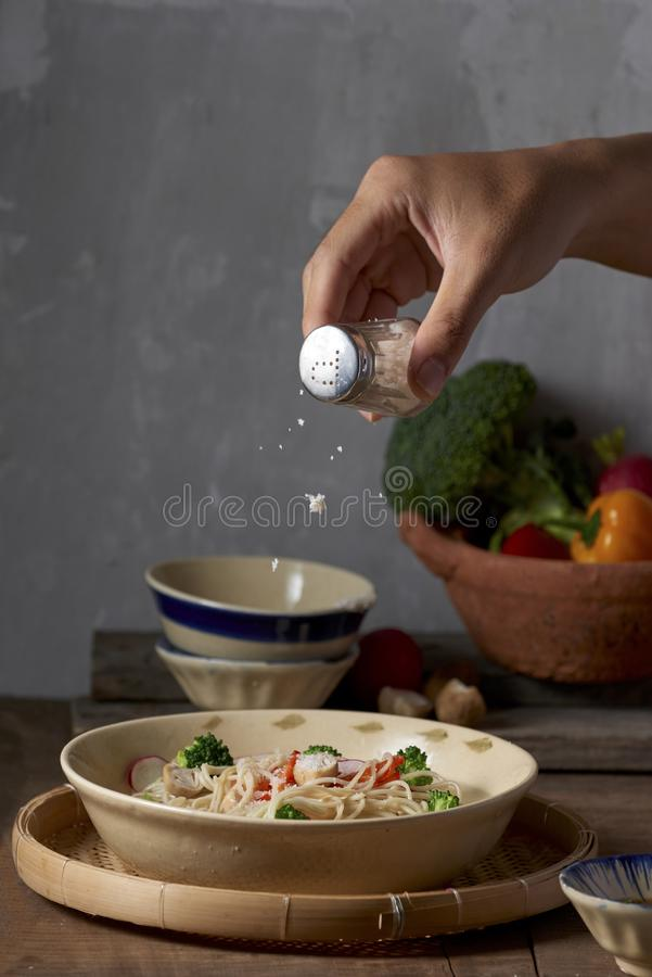 Weibliche Hand wirft Salz vom Salzkeller in die Weinleseplatte der Nudel mit Soße, gedient über altem Holztisch Dunkle rustikale  lizenzfreie stockbilder
