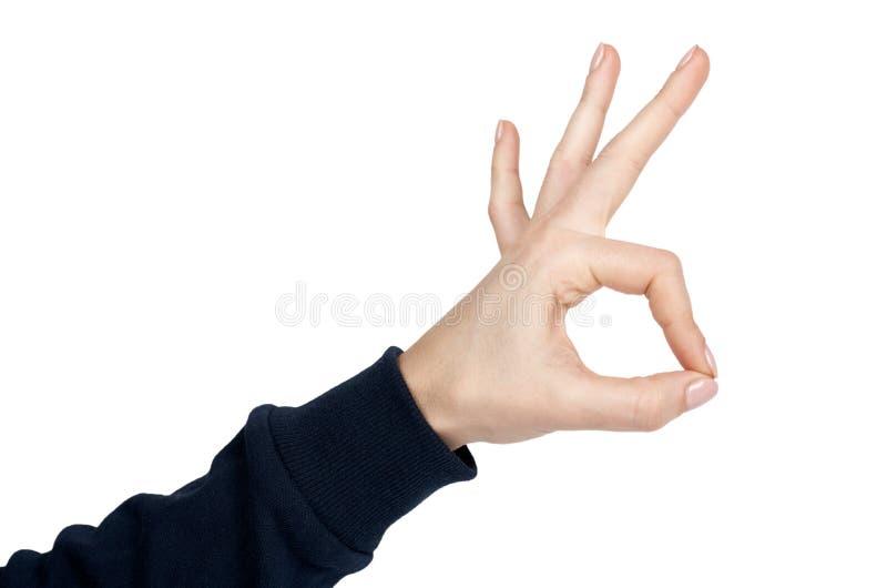 Weibliche Hand zeigt OKAY Geste und Zeichen Getrennt auf weißem Hintergrund Dunkelblauer Pullover lizenzfreies stockbild