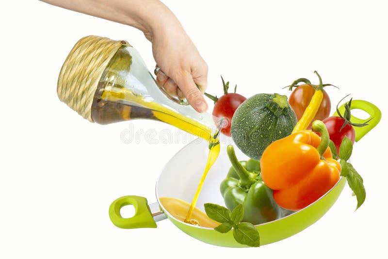 Weibliche Handauslaufendes Pflanzenöl von einer Flasche in eine Bratpfanne mit Gemüse Getrennte Nachrichten auf wei?em Hintergrun stockbilder