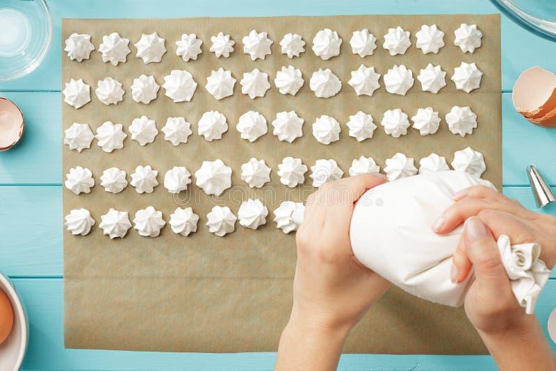 Weibliche Handpressungsschlagsahne auf Backpapier lizenzfreies stockfoto