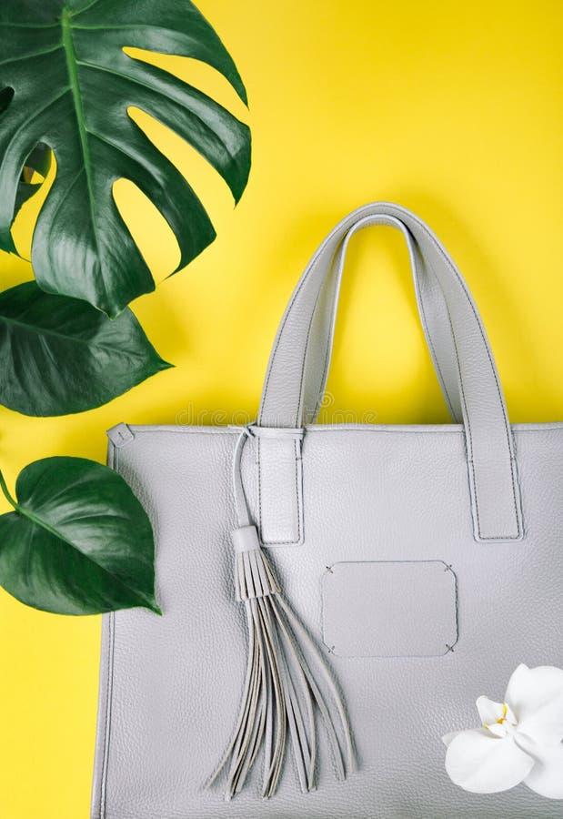 Weibliche Handtasche mit nat?rlichen Blumen und gr?nem Blatt lizenzfreie stockbilder